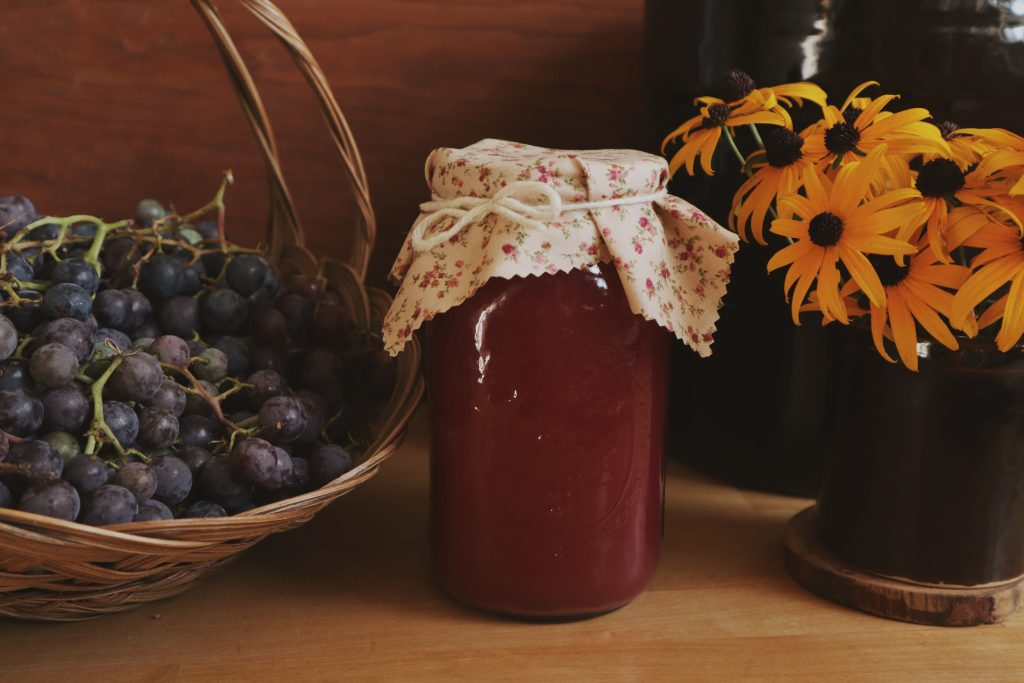 Verity Folk School Can of Homemade Grape Juice On a Wooden Counter with a basket of grapes and a crock of Black-eyed Susans