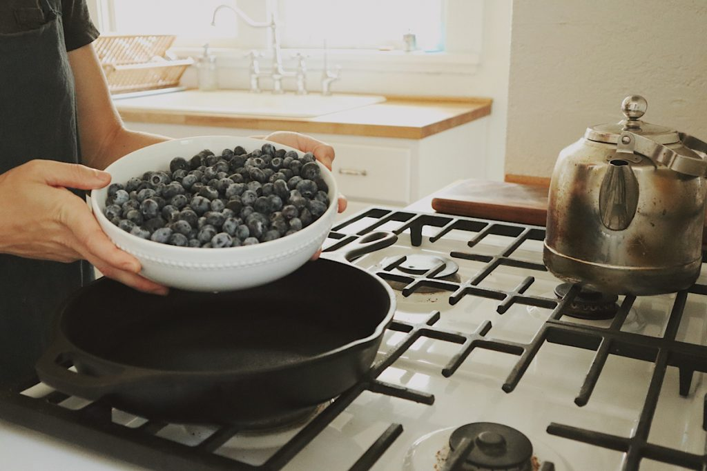Verity Folk School woman pouring blueberries into a cast iron skillet