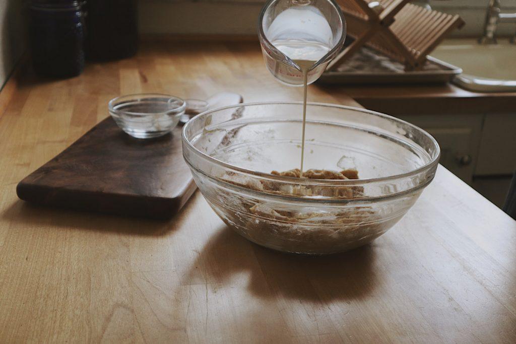 Verity Folk School woman pouring cream into a bowl with sourdough cobbler dough