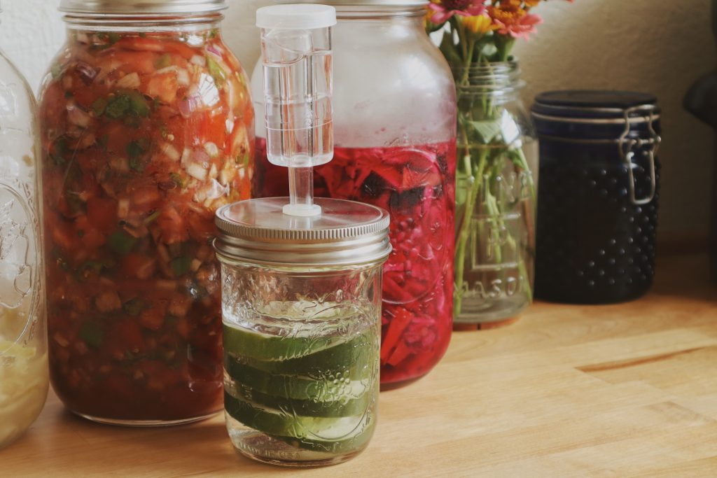 Verity Folk School Lacto Fermented crock pickles and other fermented foods in a kitchen on a butcher block counter