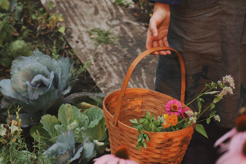 Verity Folk School a woman carrying a woven basket in a garden