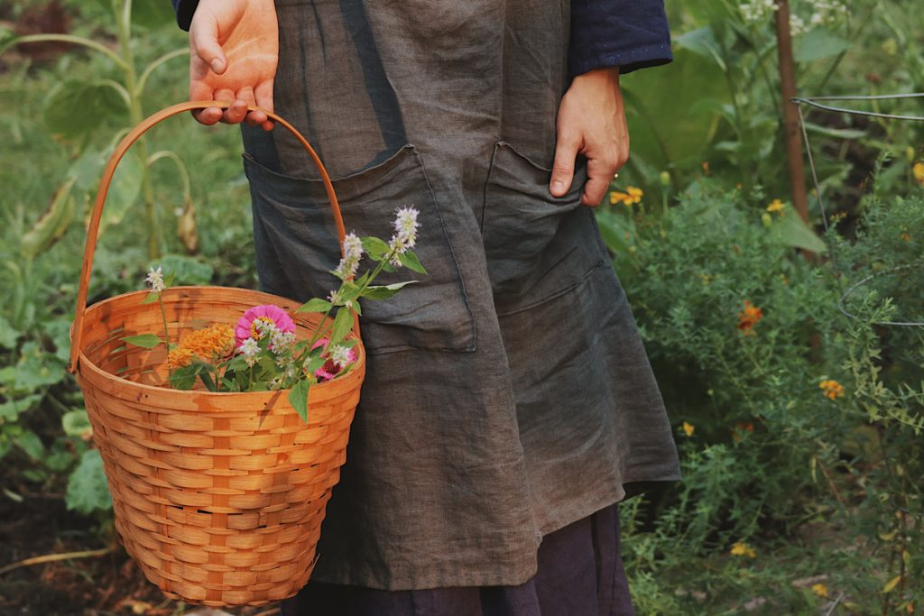 Verity Folk School woman wearing blue apron standing in a garden holding a basket filled with flowers