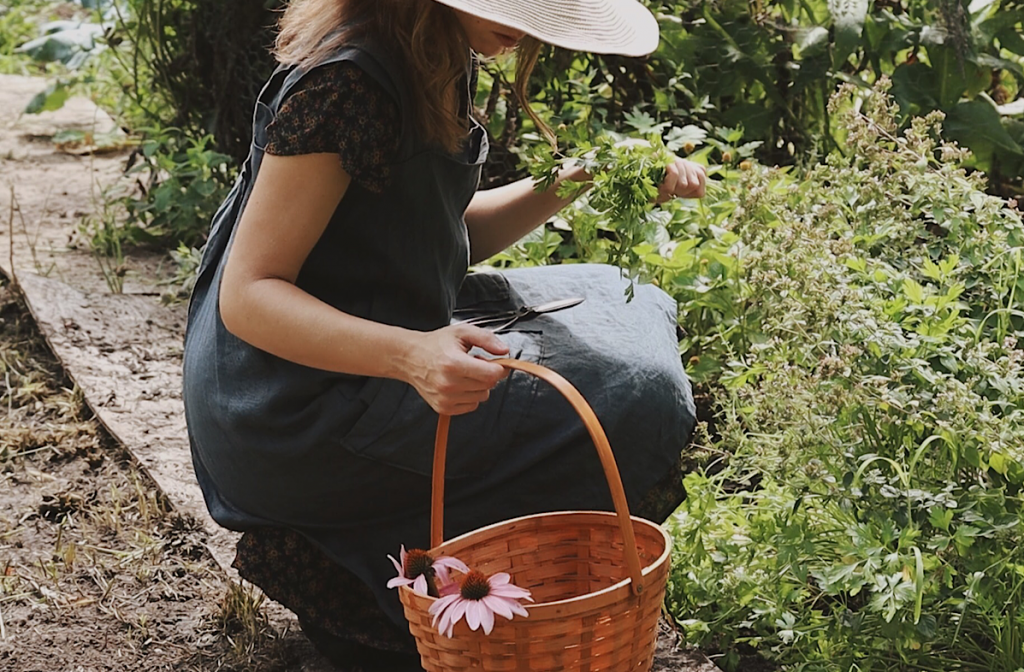 Verity Folk School woman in a garden with woven basket and fresh herbs