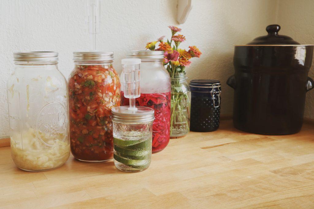 Verity Folk School Lacto Fermented Foods In Mason Jars on a wood counter