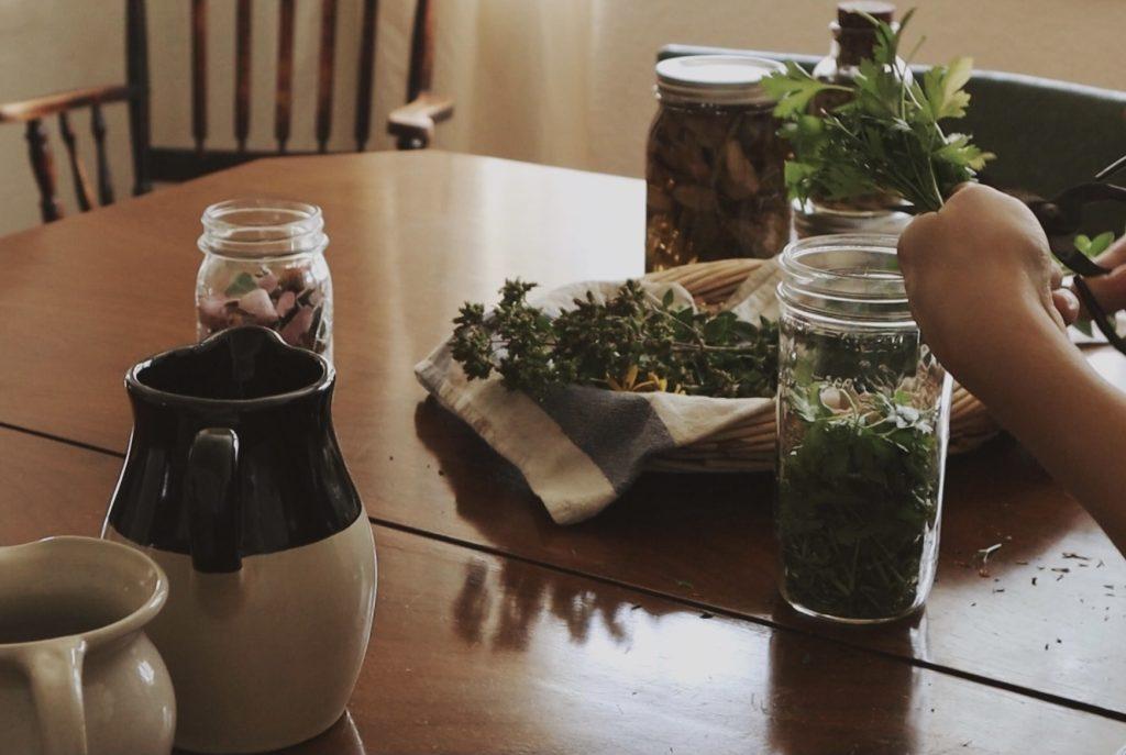 Verity Folk School woman chopping herbs into a glass jar