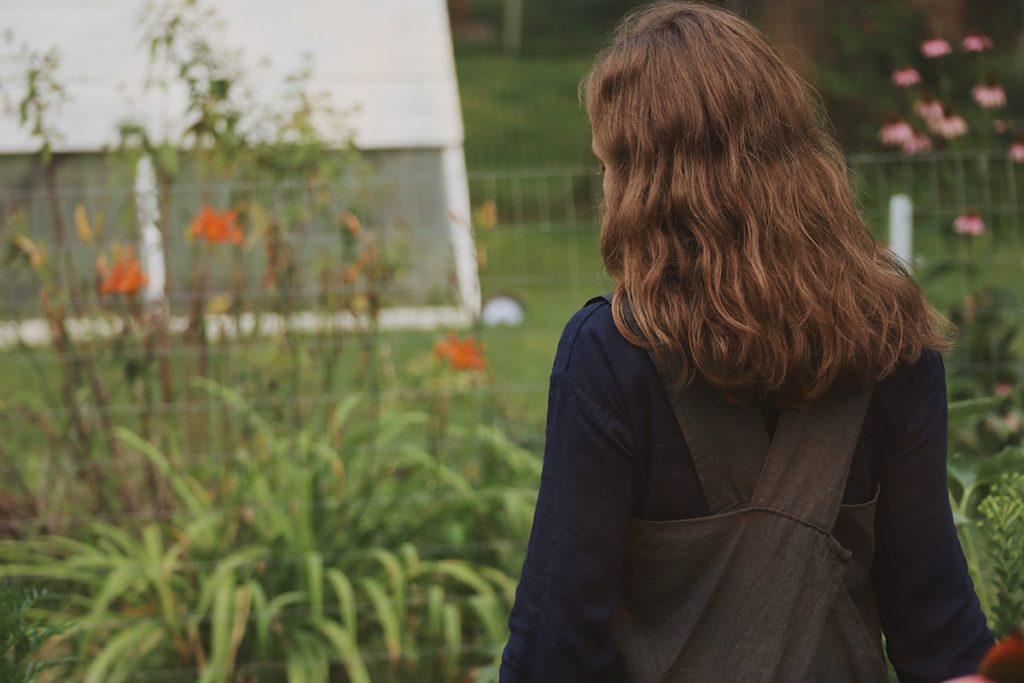 Verity Folk School woman in a blue dress walking in a garden