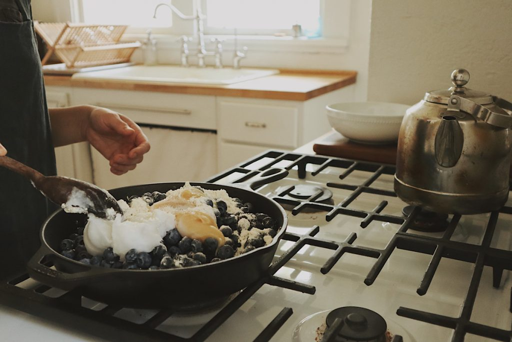 Verity Folk School woman stirring blueberries, honey and butter in a cast iron skillet