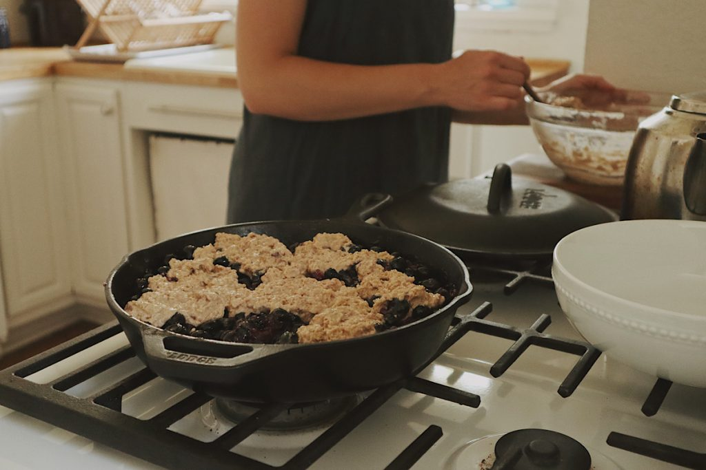Verity Folk School woman spooning dough onto blueberries