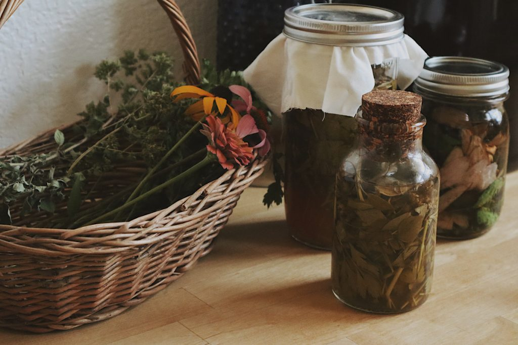 Verity Folk School herbal remedies for immune support in glass jars on a butcher block counter top with a basket of flowers