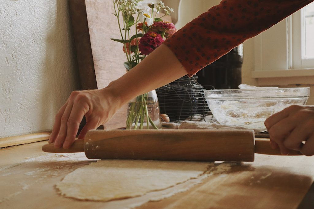 Verity Folk School woman wearing a red dress rolling out handmade egg noodle dough on a wooden counter