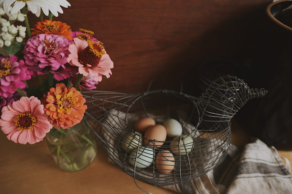 Verity Folk School wire basket of farm fresh eggs with a vase of zinnias on a wooden counter