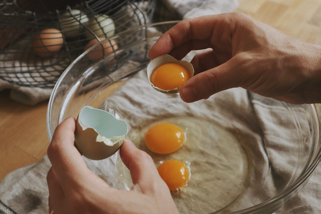 Verity Folk School woman adding farm fresh eggs to a glass mixing bowl