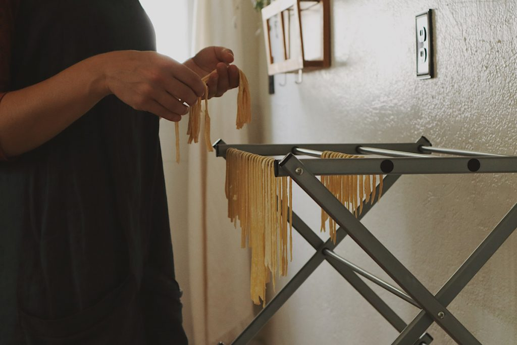 Verity Folk School woman wearing a blue linen apron hanging old fashioned handmade egg noodles to dry on a drying rack