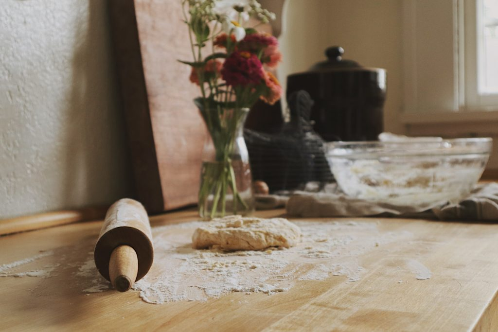 Verity Folk School egg noodle dough on a floured wood countertop with a wood rolling pin and a vase of fresh flowers