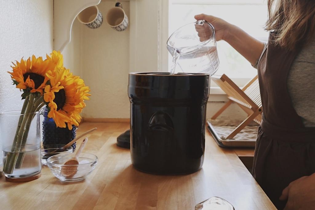 Verity Folk School woman pouring salt water brine into a brown ceramic fermenting crock