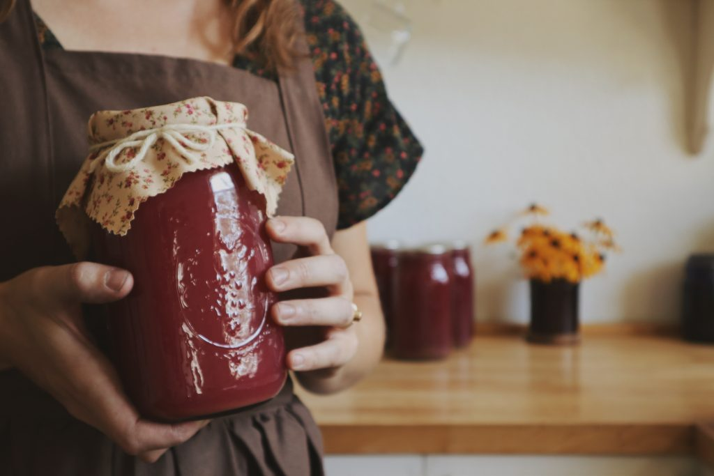 Verity folk school woman holding a jar of homemade grape juice in a brown pinafore apron in a kitchen with flowers in the background