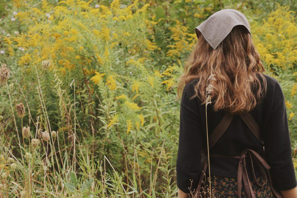 Verity Folk School woman standing in a meadow of goldenrod