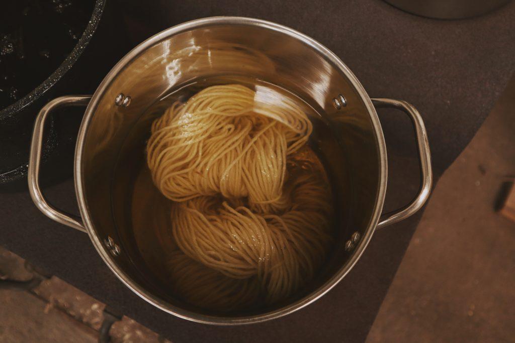 Verity Folk School wool yarn simmering in a dye pot of goldenrod