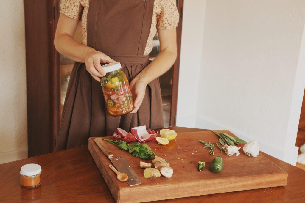 Verity Folk School woman wearing handmade clothing holding a jar of homemade herbal remedy
