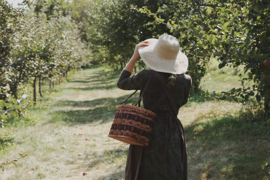 Verity Folk School woman in a green dress and straw hat in an apple orchard